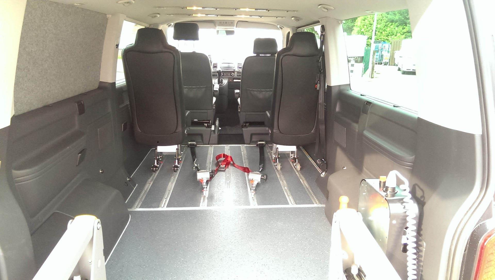 Particuliere rolstoelvervoer met rolstoel TUSSEN de achter stoelen, daardoor tussen de voorstoelen doorkijken.